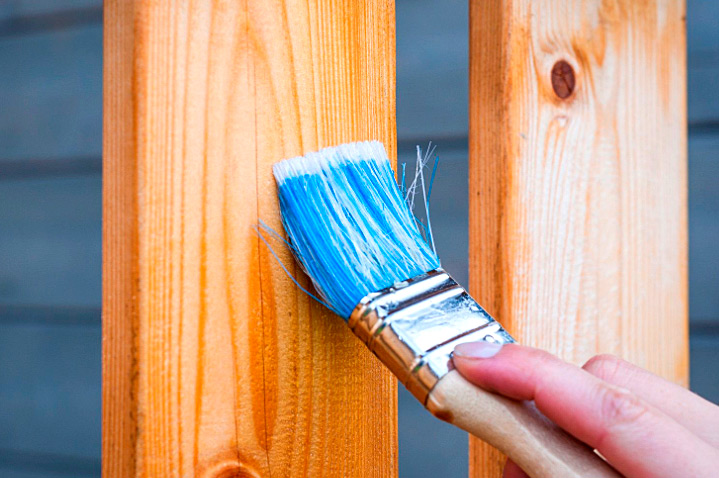 a painter painting a wooden fence